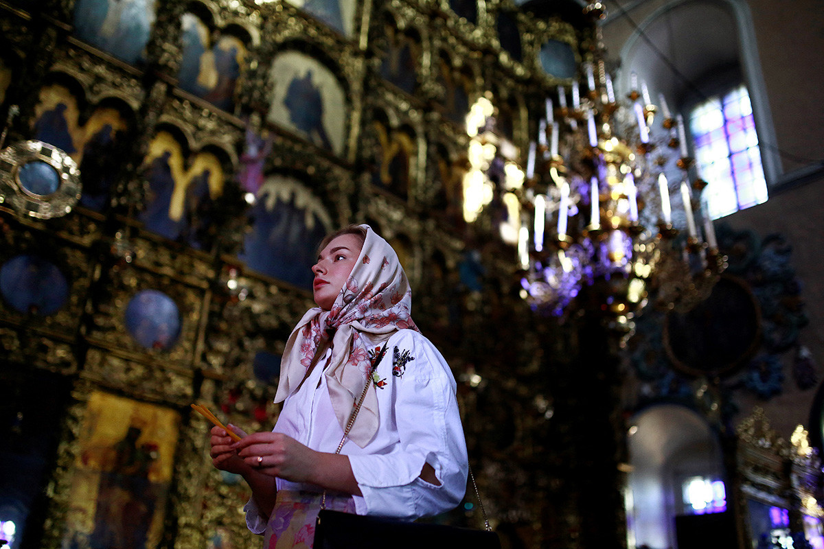 A woman gives a prayer in the Saint Peter and Saint Paul church in Kazan
