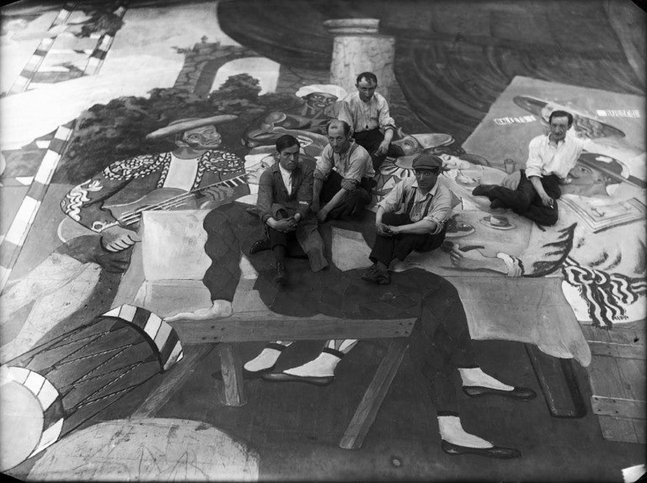 Picasso et les artistes de scène, assis sur un tissu du décor du ballet Parade, au théâtre du Châtelet, Paris, 1917