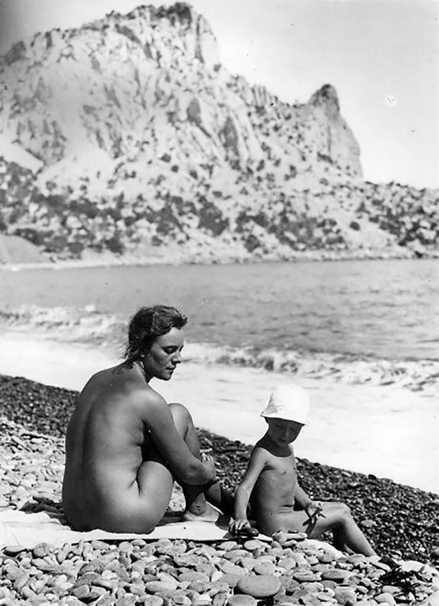 Eine Frau und ihr Kind sonnen sich an einem Strand auf der Krim, 1925.