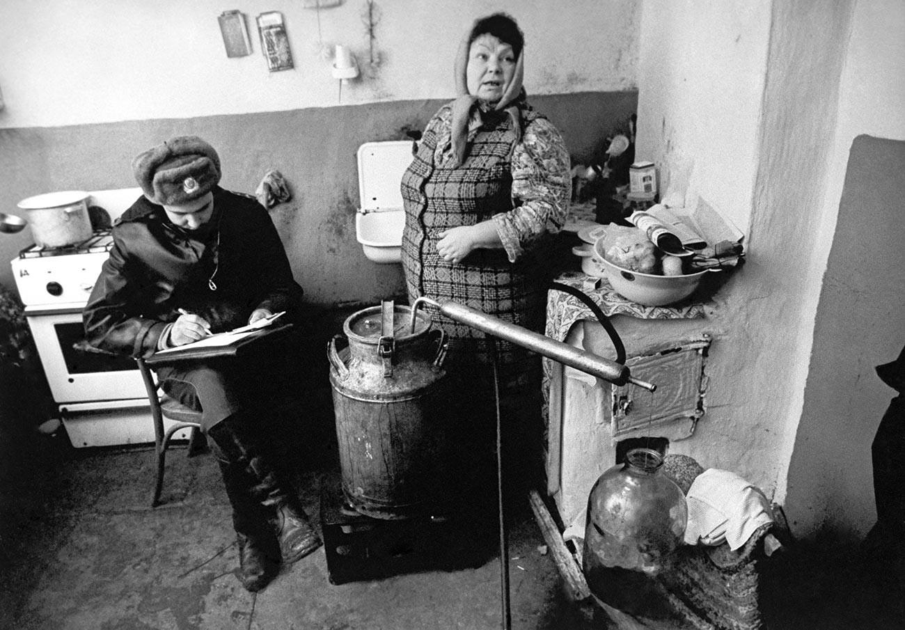 Полицајац саставља записник у селу где се по кућама врши нелегална производња јаког алкохолног пића (самогона).