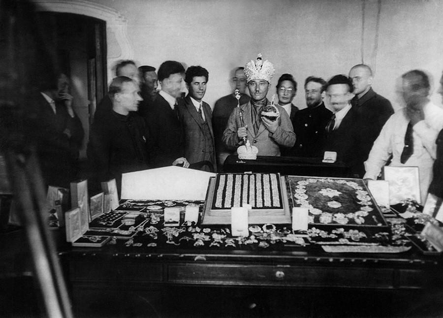 Convidado estrangeiro experimenta coroa de imperadores russos, tendo em mãos o cetro e o orbe.