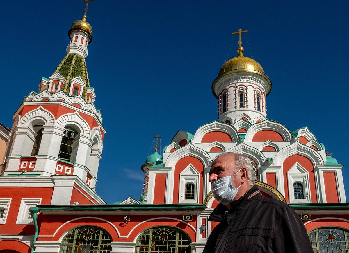 Un signore con la mascherina contro il Covid passa davanti a una cattedrale ortodossa in Piazza Rossa a Mosca, 2 ottobre 2020