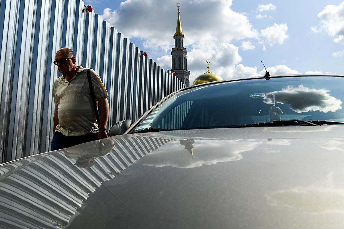 Un uomo cammina vicino alla recinzione che circonda un cantiere nei pressi della moschea Sobornaja, Mosca, 7 agosto 2019
