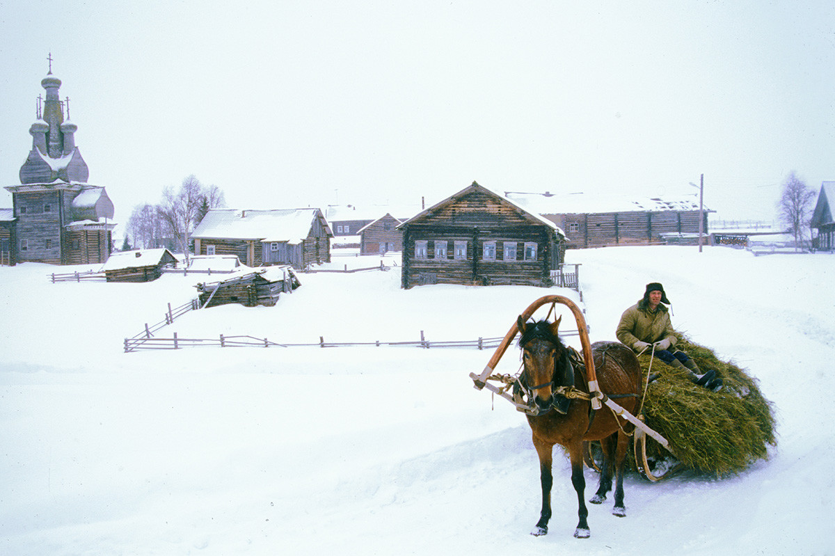 Kimzha village. Church of the Hodegetria Icon, log houses & stables (background). March 7, 2000