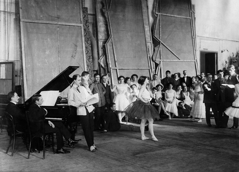 Ballets Russes during the rehearsal: at the piano on the right is composer Igor Stravinsky, and standing is Michael Fokine. In the center is ballerina Tamara Karsavina.