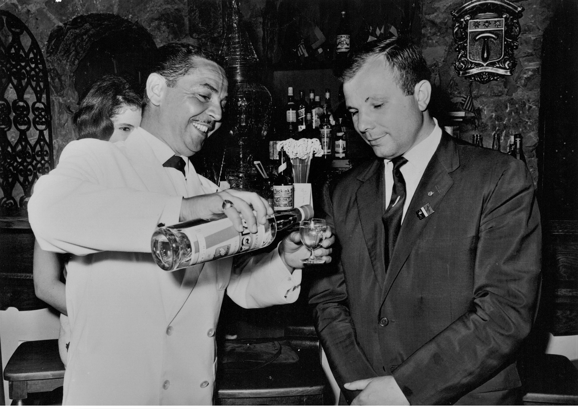 Gagarine prêt à déguster un pastis Ricard que le serveur est en train de lui verser dans un verre. La photo est prise  dans le bar de l'hôtel Delos de l'île de Bendor