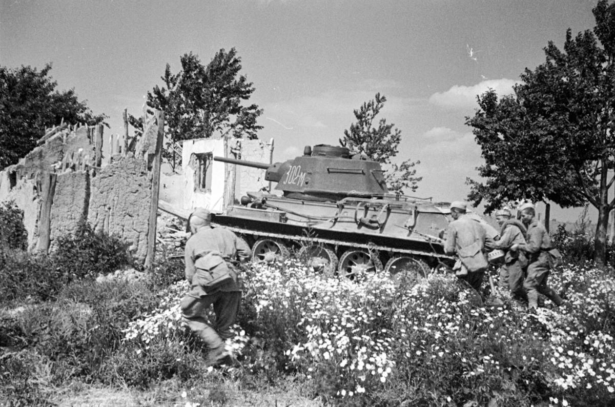 Un groupe de fantassins soviétiques couverts par un char passe à l'offensive en périphérie de Bucarest