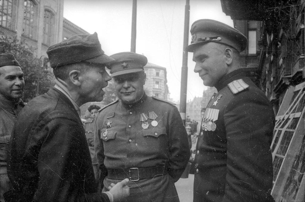 Des officiers soviétiques discutent avec des habitants de Berlin