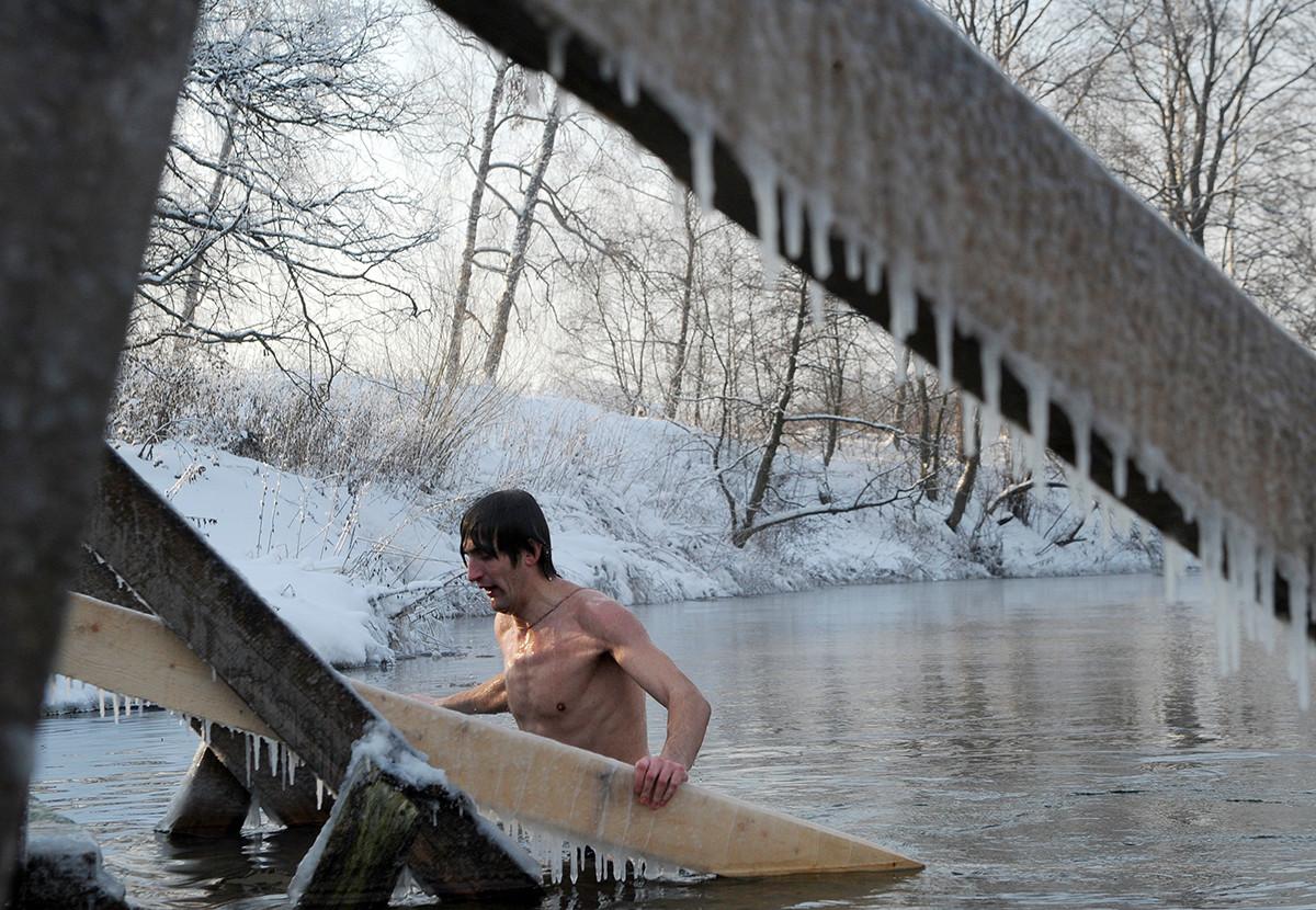 正教会の公現祭で冷たい水に浸かる男性