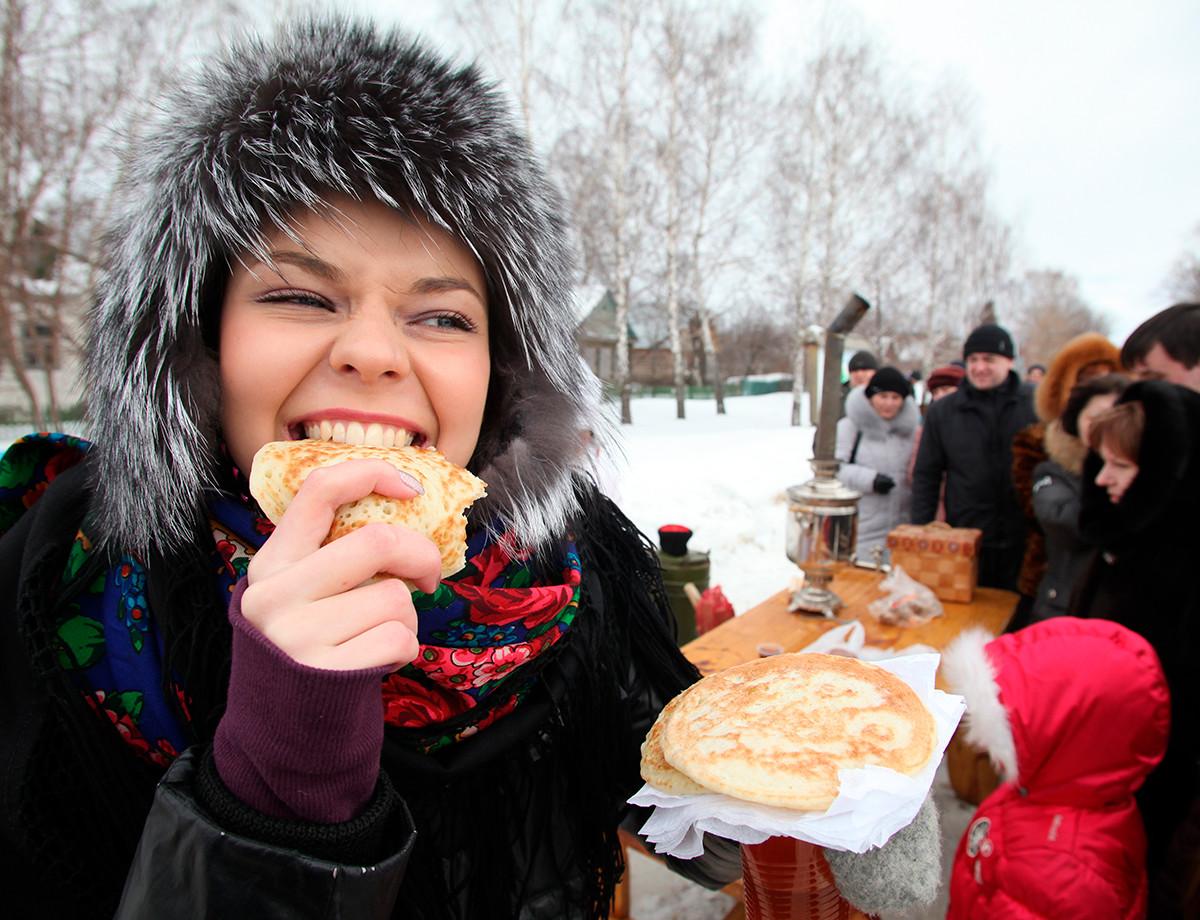リャザンにて、マースレニツァ(バター祭り)でブリヌィ(パンケーキ)を楽しむ若い女性