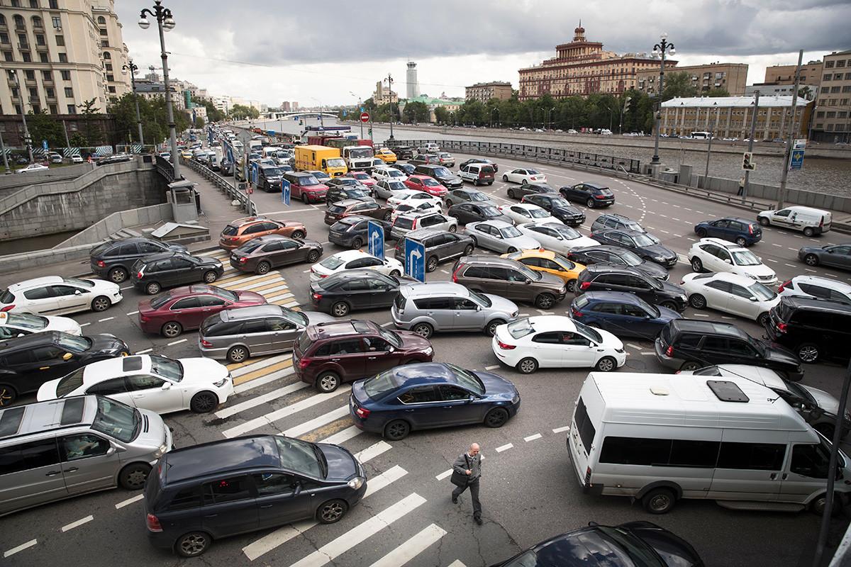 Čovjek prelazi ulicu u tijeku prometne gužve na obali rijeke Moskve u centru Moskve.