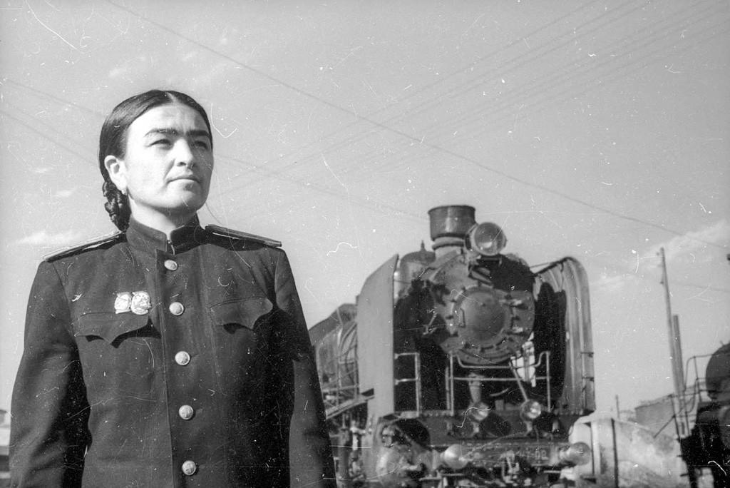 機関車の傍でポーズをとる運転士グリアム・ガサノワ