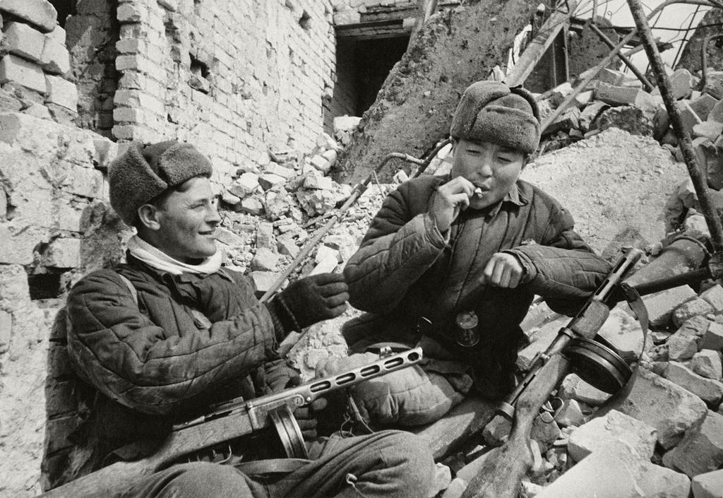 スターリングラードで煙草を分け合って吸う武装した仲間