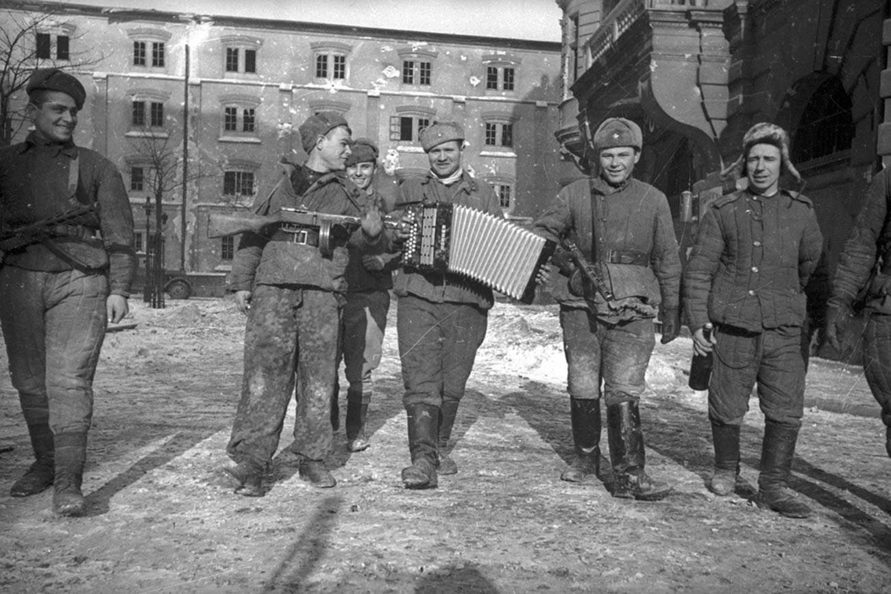 Des soldats soviétiques avec un accordéon célèbrent la libération de la ville