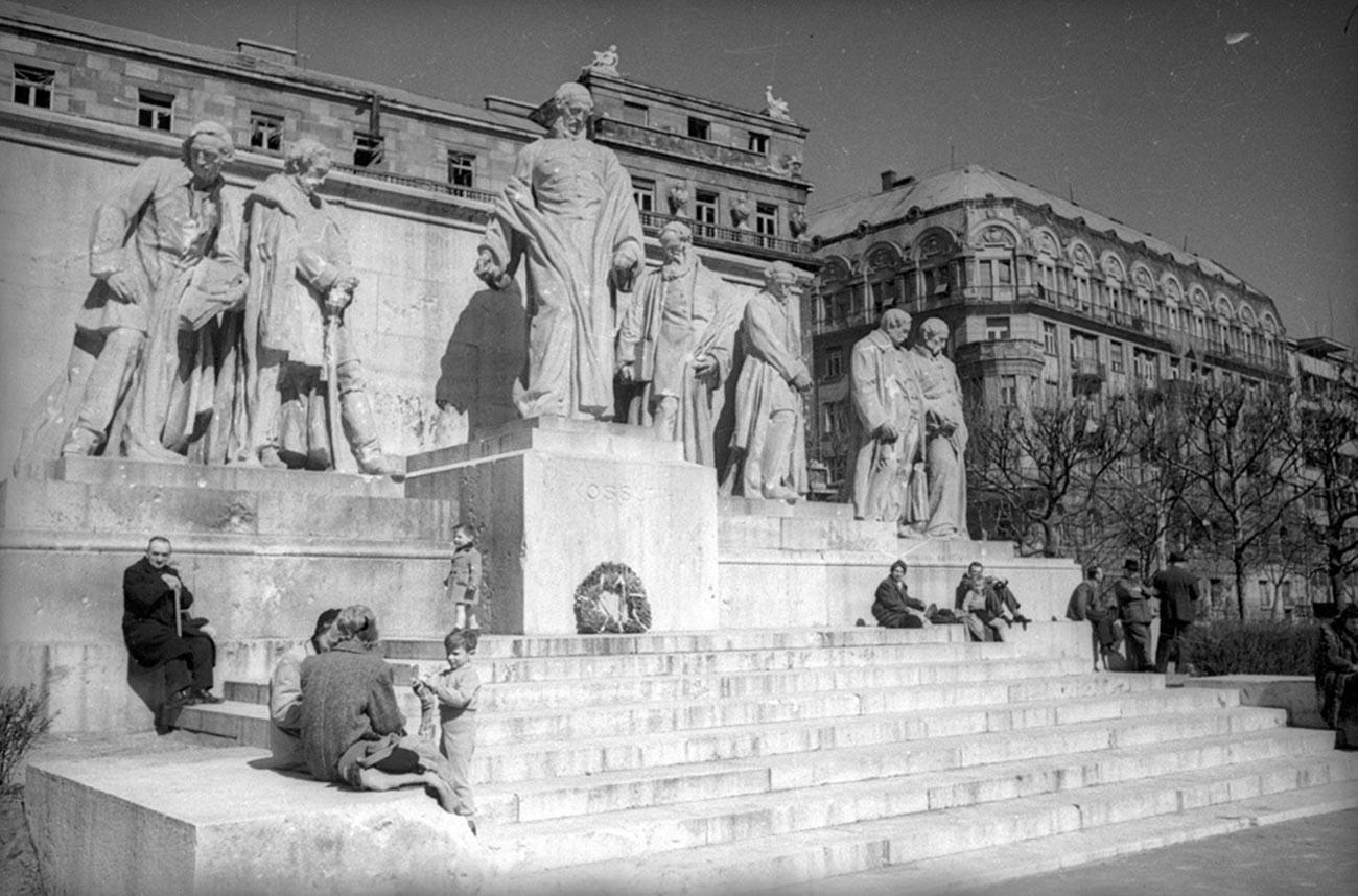Des habitants de Budapest à côté du monument à Lajos Kossuth, président-gouverneur de Hongrie du XIXe siècle