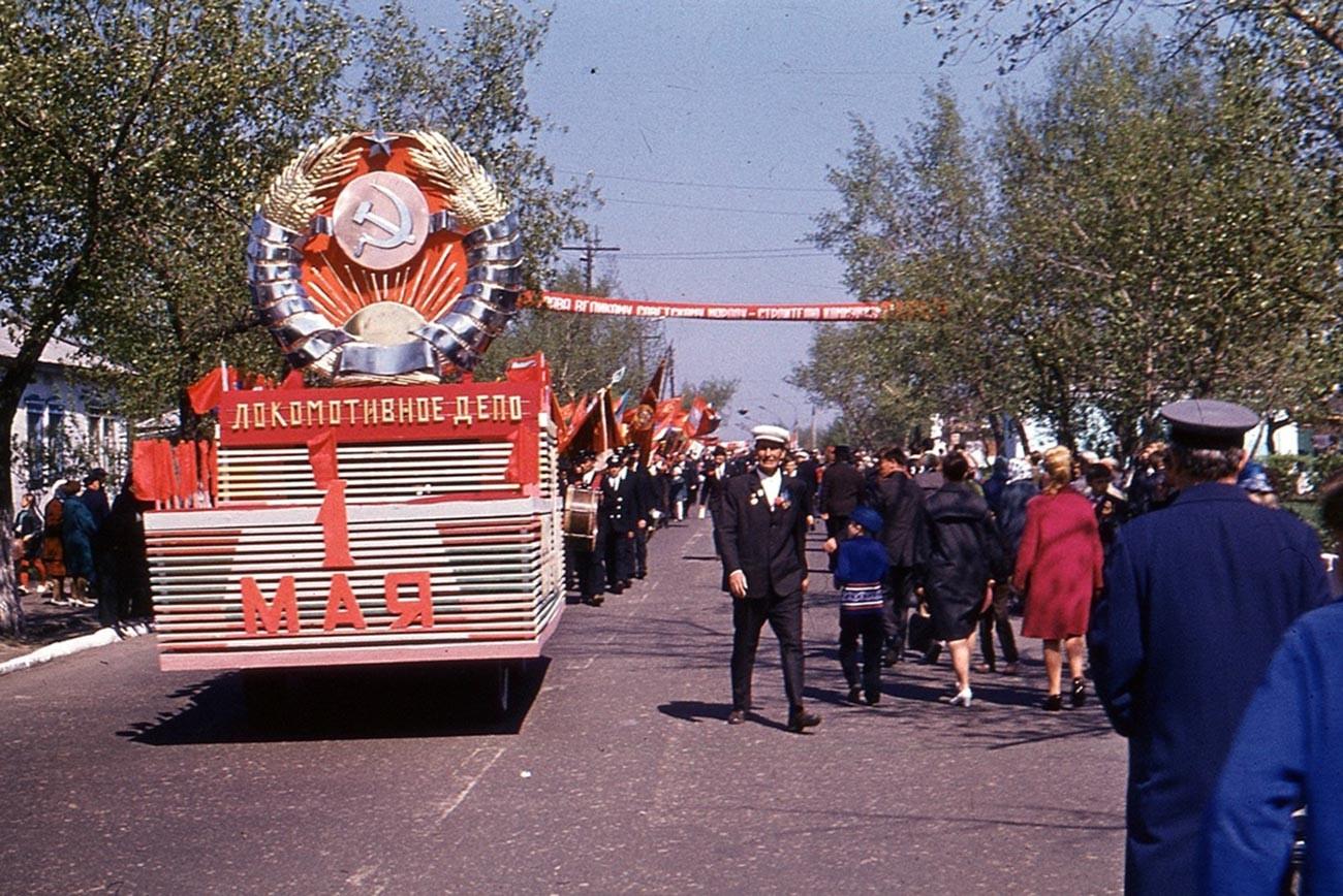 Des employés du dépôt de locomotives de la ville de Voronej marchent dans les rues avec les drapeaux rouges et des décorations, 1970