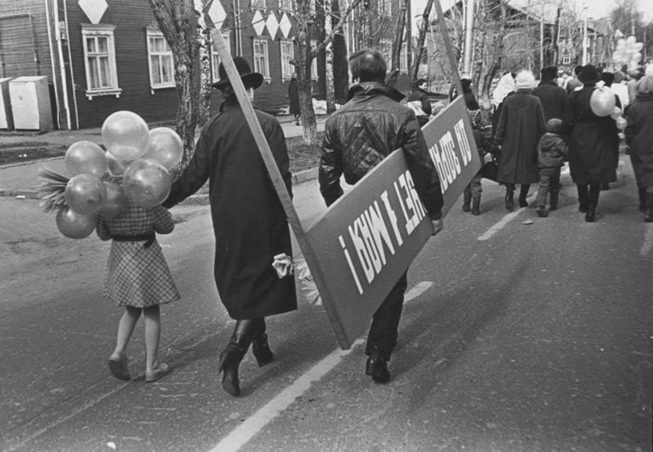 Un homme avec une pancarte «Vive le 1er mai» se rend à une manifestation avec sa famille, 1987