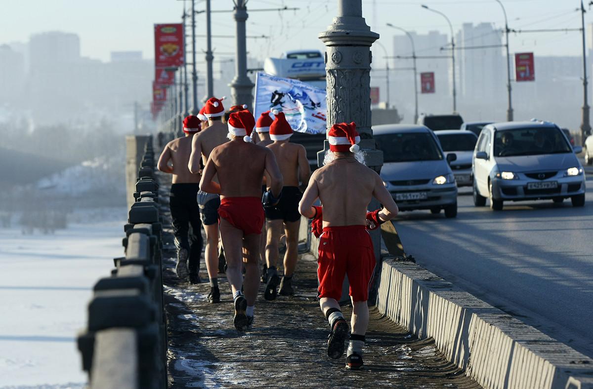Des joggeurs en tenues de Père Noël traversent le fleuve Ob à Novossibirsk, la capitale de Sibérie