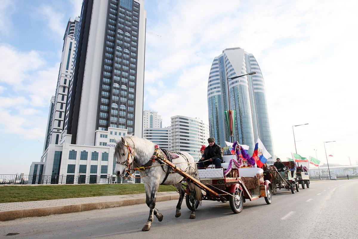 Des voitures à cheval passent devant les bâtiments récemment achevés du centre d'affaires Grozny-City Towers de la ville de Grozny, la capitale de la république de Tchétchénie.