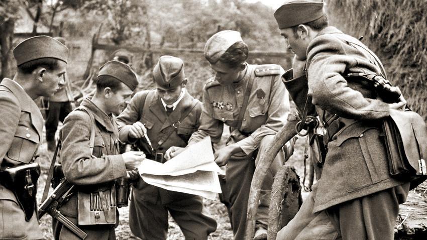 Simbolična slika: Štab brigade jugoslovanskih partizanov in oficir Sovjetske armade sprejemajo odločitev pred bojem, oktober 1944