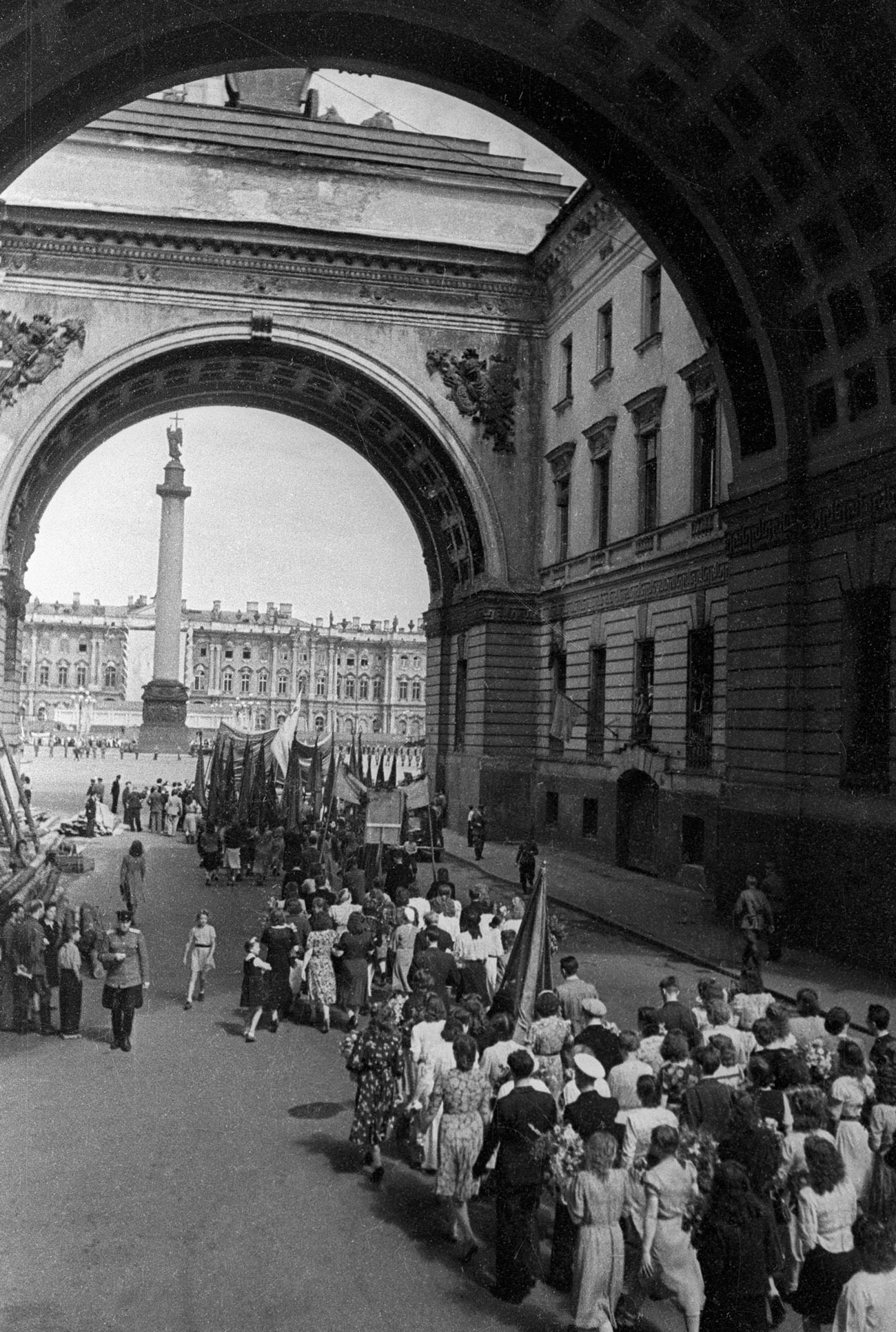 Колонна демонстрантов проходит под Триумфальной аркой главного штаба в Ленинграде.
