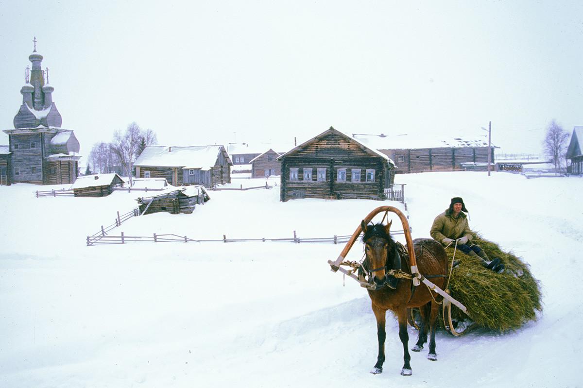 Village de Kimja. Église de l'Icône de la Vierge Hodegetria, maisons en rondins et écuries (arrière-plan)