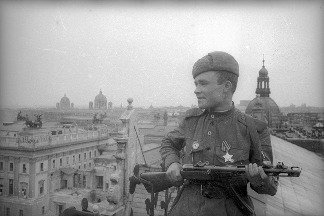 Un soldat soviétique posant sur le toit de l'un des bâtiments de la ville