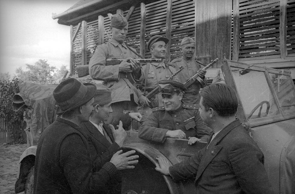 Des officiers soviétiques parlent aux habitants de la ville.