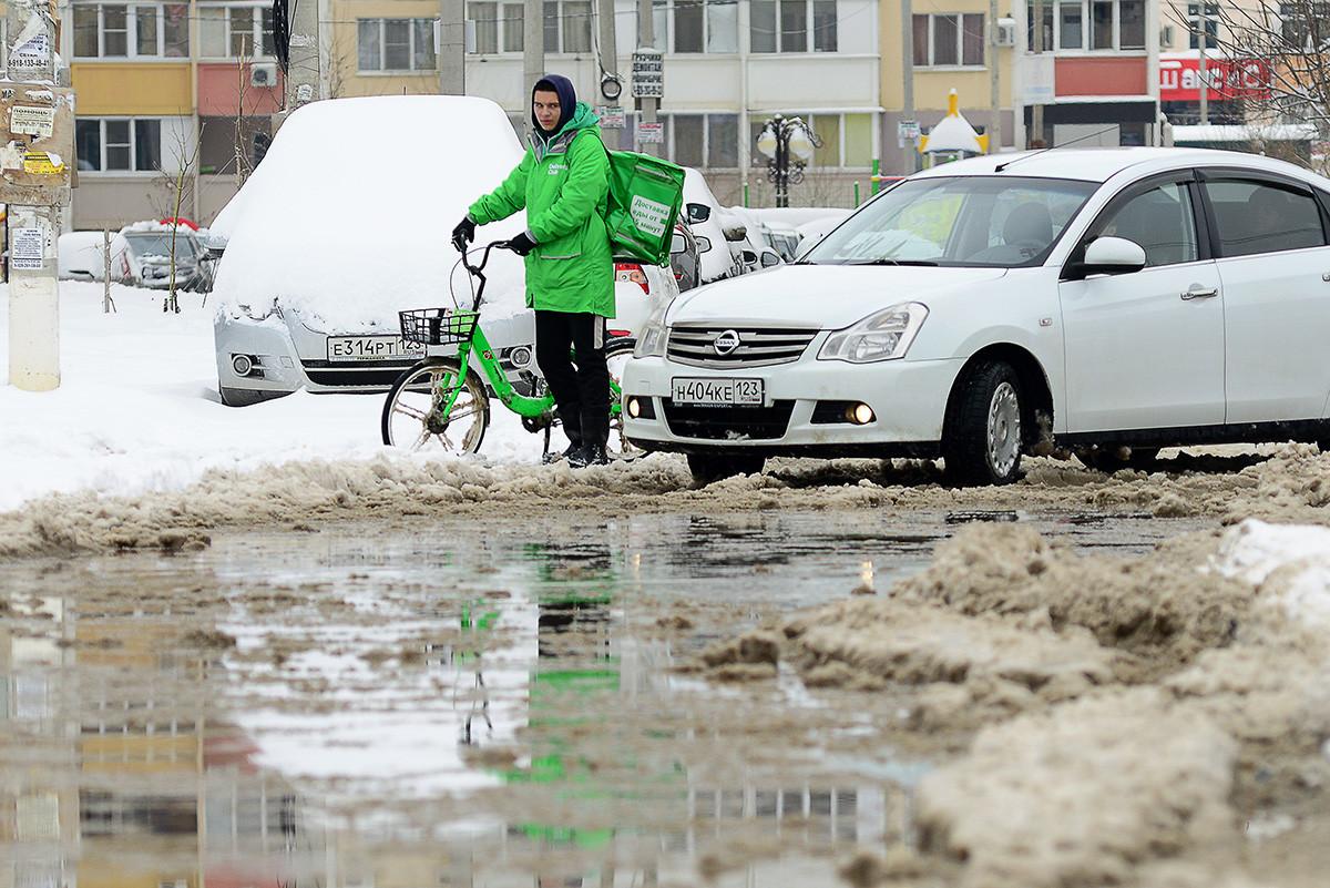Краснодар, 7 февраля 2021 года: курьер на улице после снегопада. С вечера 6 февраля в городе шел дождем со снегом, аэропорт города закрыт