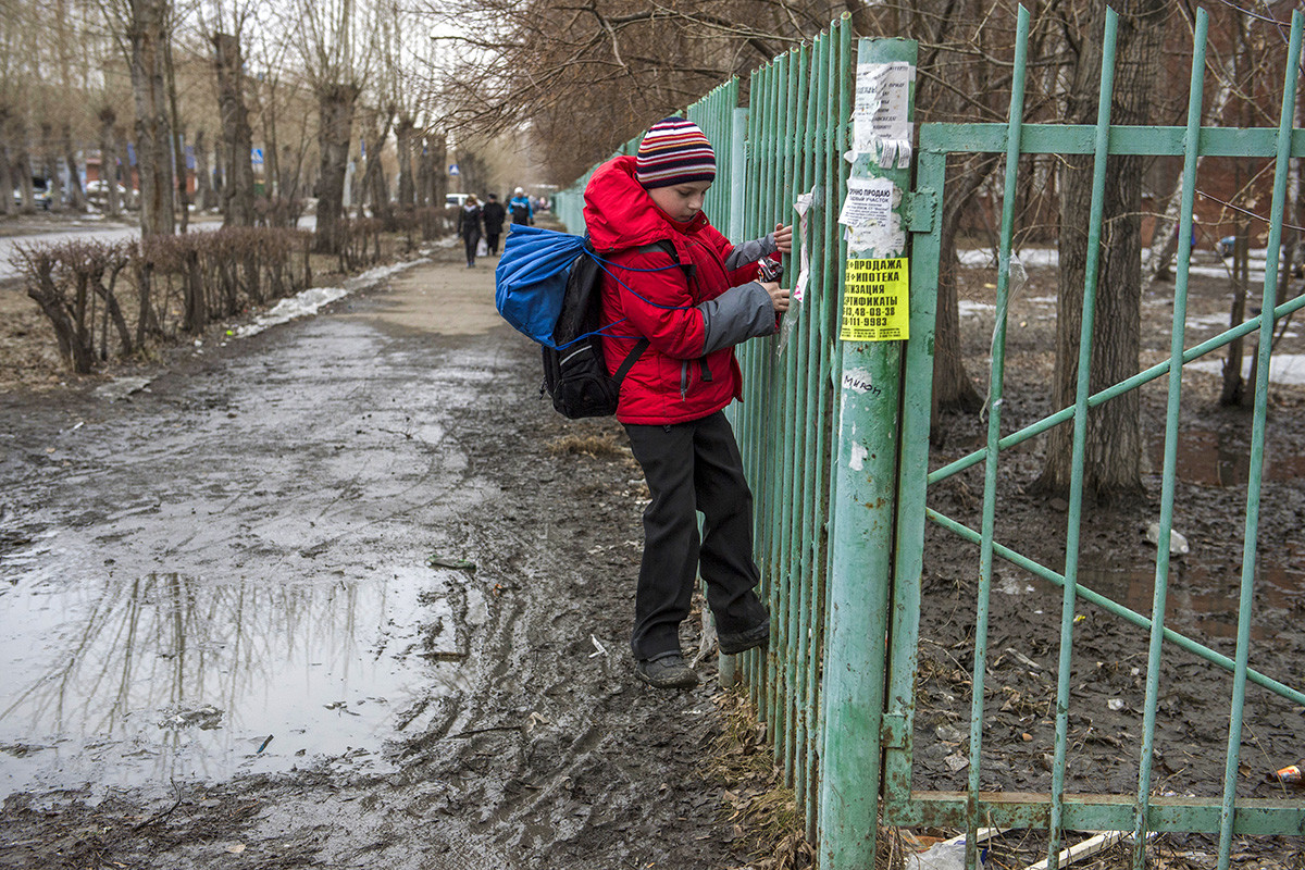 A child crosses a puddle on one of the streets of Omsk