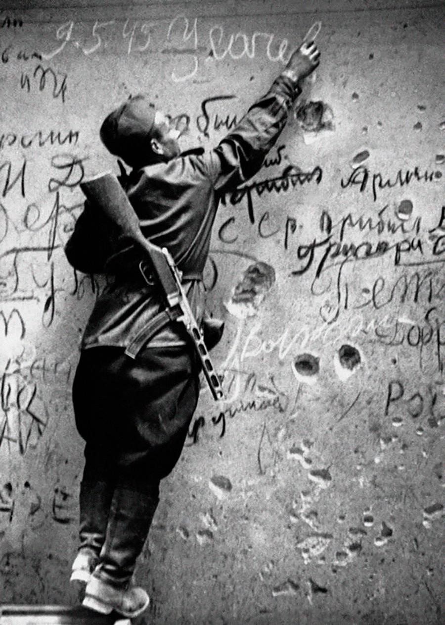 Un soldat soviétique laissant une signature sur le mur du Reichstag