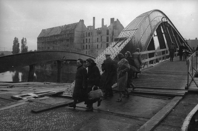 Des habitants traversant un pont endommagé