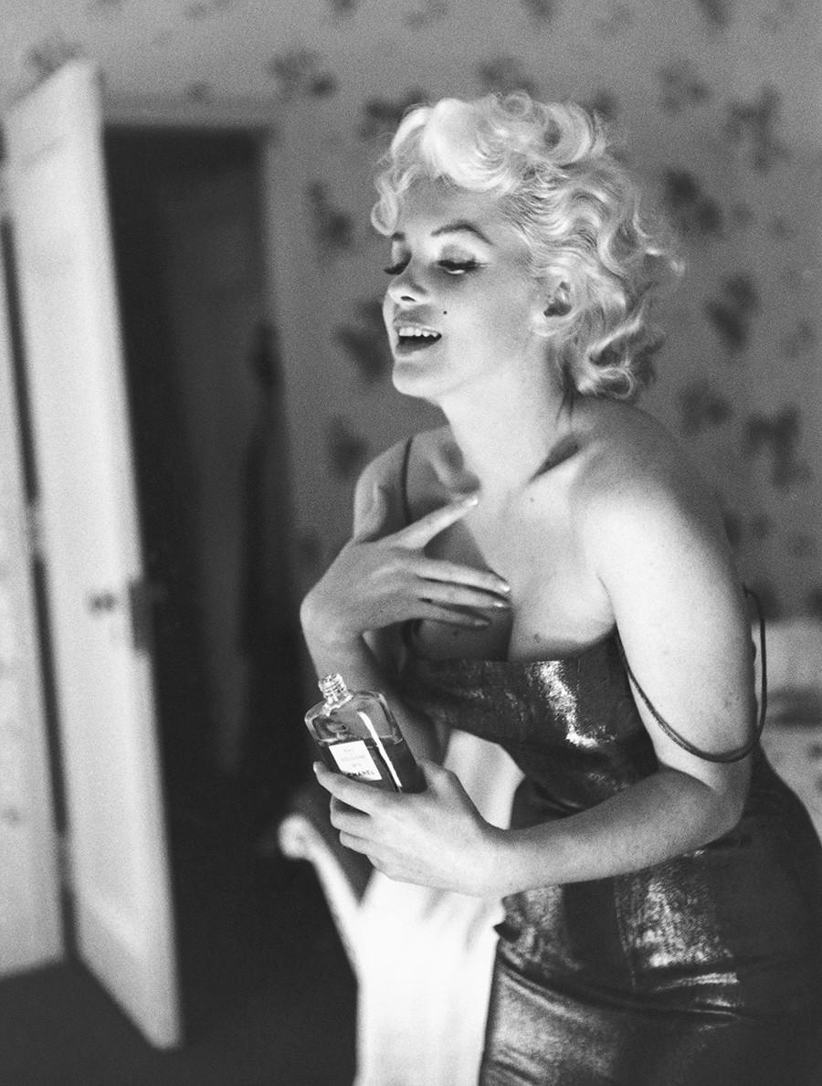 Marilyn Monroe posant avec un flacon de Chanel N°5