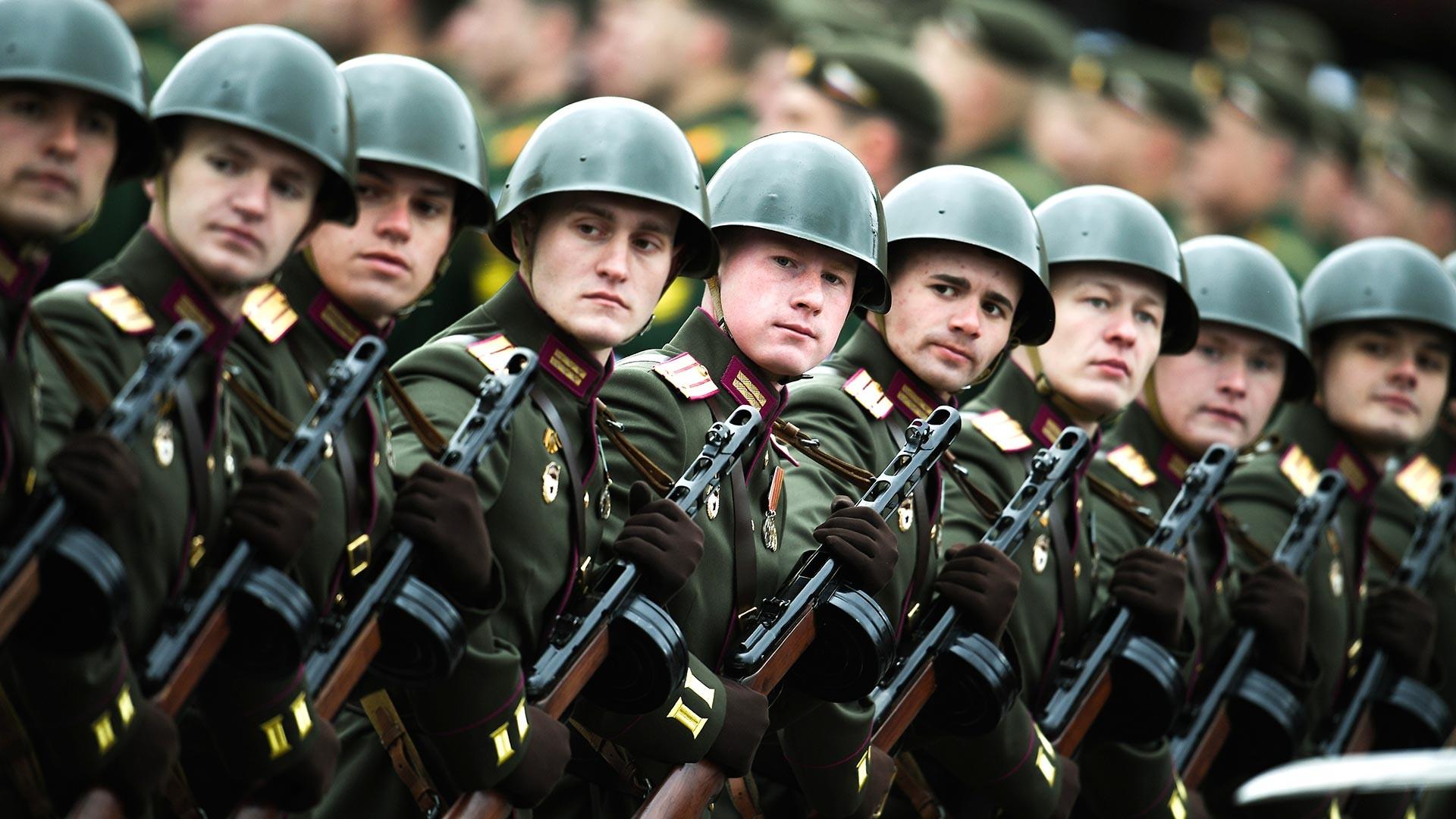 Des militaires russes traversant la place Rouge en portant des uniformes soviétiques de la Seconde Guerre mondiale et des mitraillettes PPSh.
