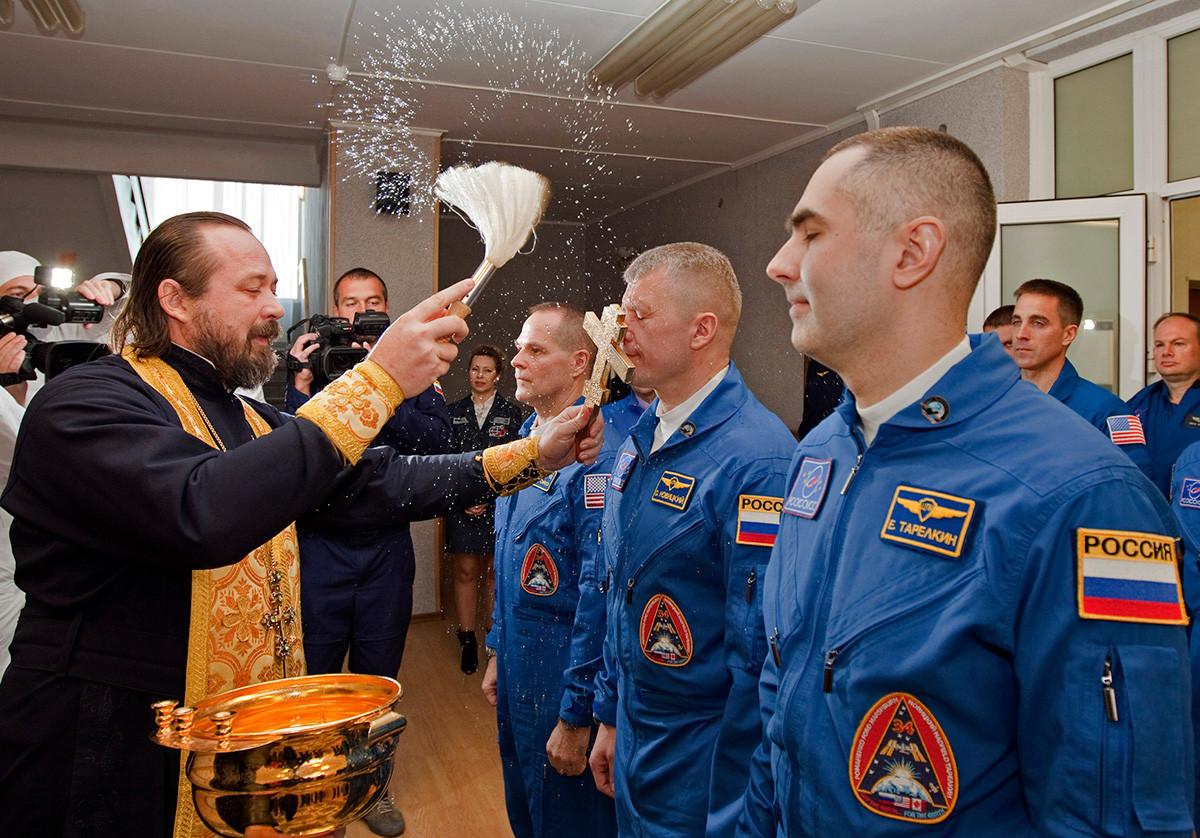 Pravoslavni duhovnik blagoslavlja člane naslednje odprave na Mednarodno vesoljsko postajo: ameriškega astronavta Kevina Forda (levo) in dva ruska kozmonavta Olega Novickega (v sredini) in Jevgenija Tarelkina (desno).