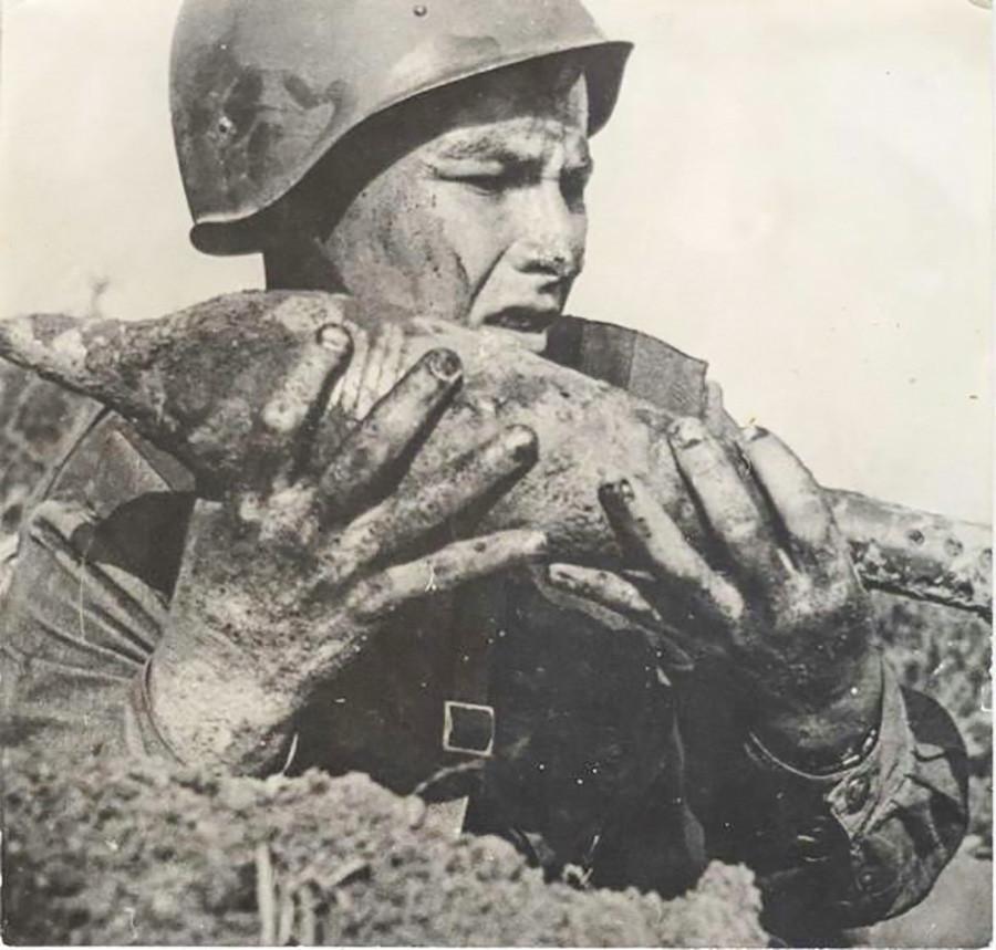 Un démineur portant une munition non explosée
