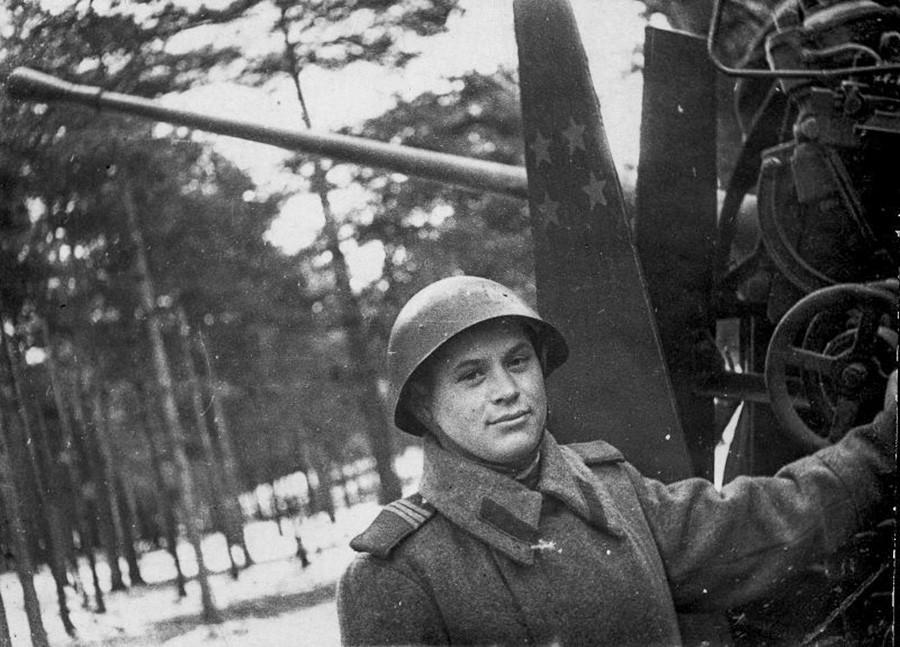 Un mitrailleur posant à côté de son arme
