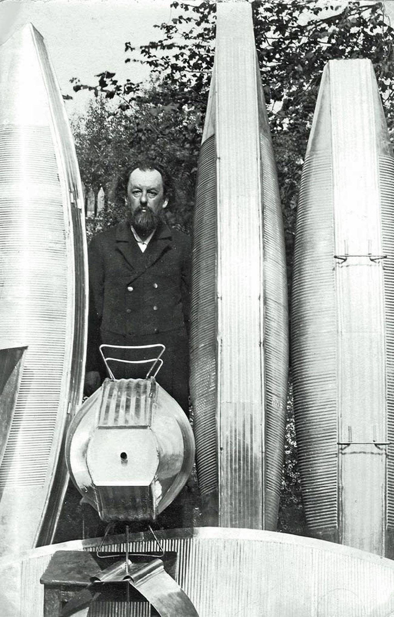 Constantin Tsiolkovski au jardin avec les modèles réduits d'un dirigeable en métal