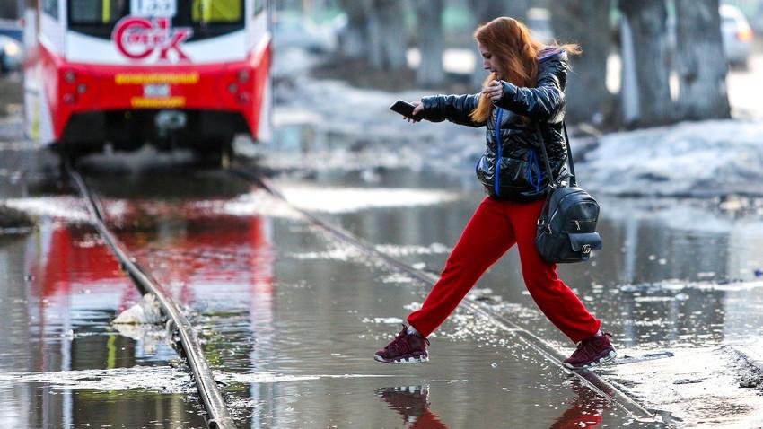 Omsk, 7. aprila 2021: Ženska preskakuje čez vodo na poplavljeni ulici. Poplave so nastale zaradi taljenja snega.
