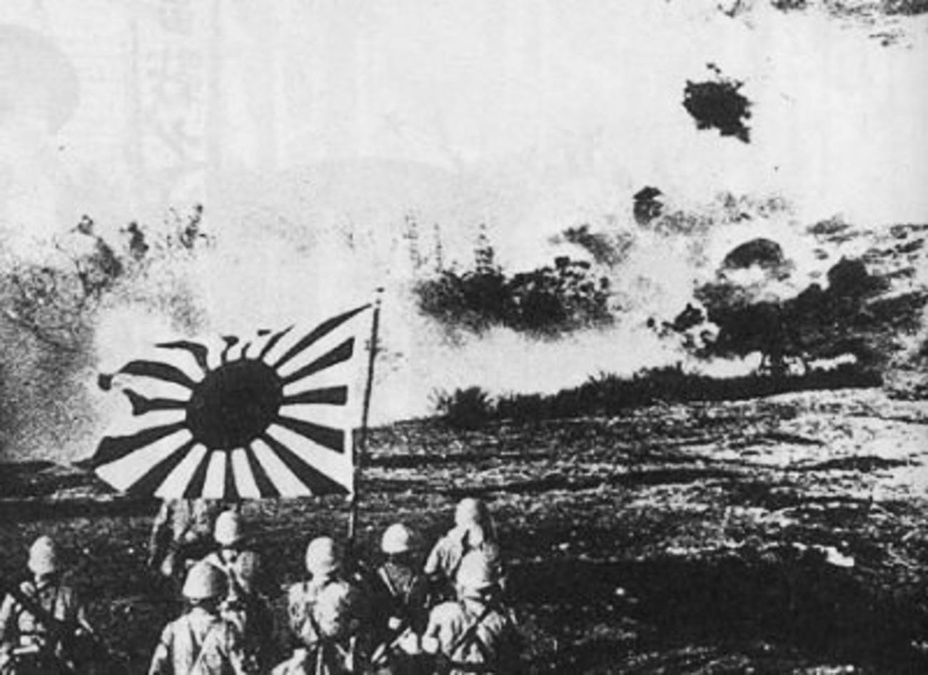 La fuerza de desembarco naval japonesa volando un fortín chino y marchando con la bandera naval durante la Operación Cantón