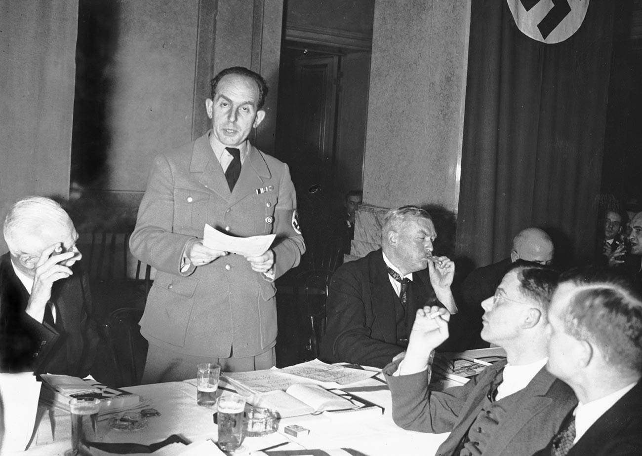На пријему у Министарству правде Рајха држи говор тадашњи државни секретар Роланд Фрајслер. С десне стране сједи министар правде Франц Гартлер, у првом плану је тадашњи лични референт министра Ханс фон Донањи.