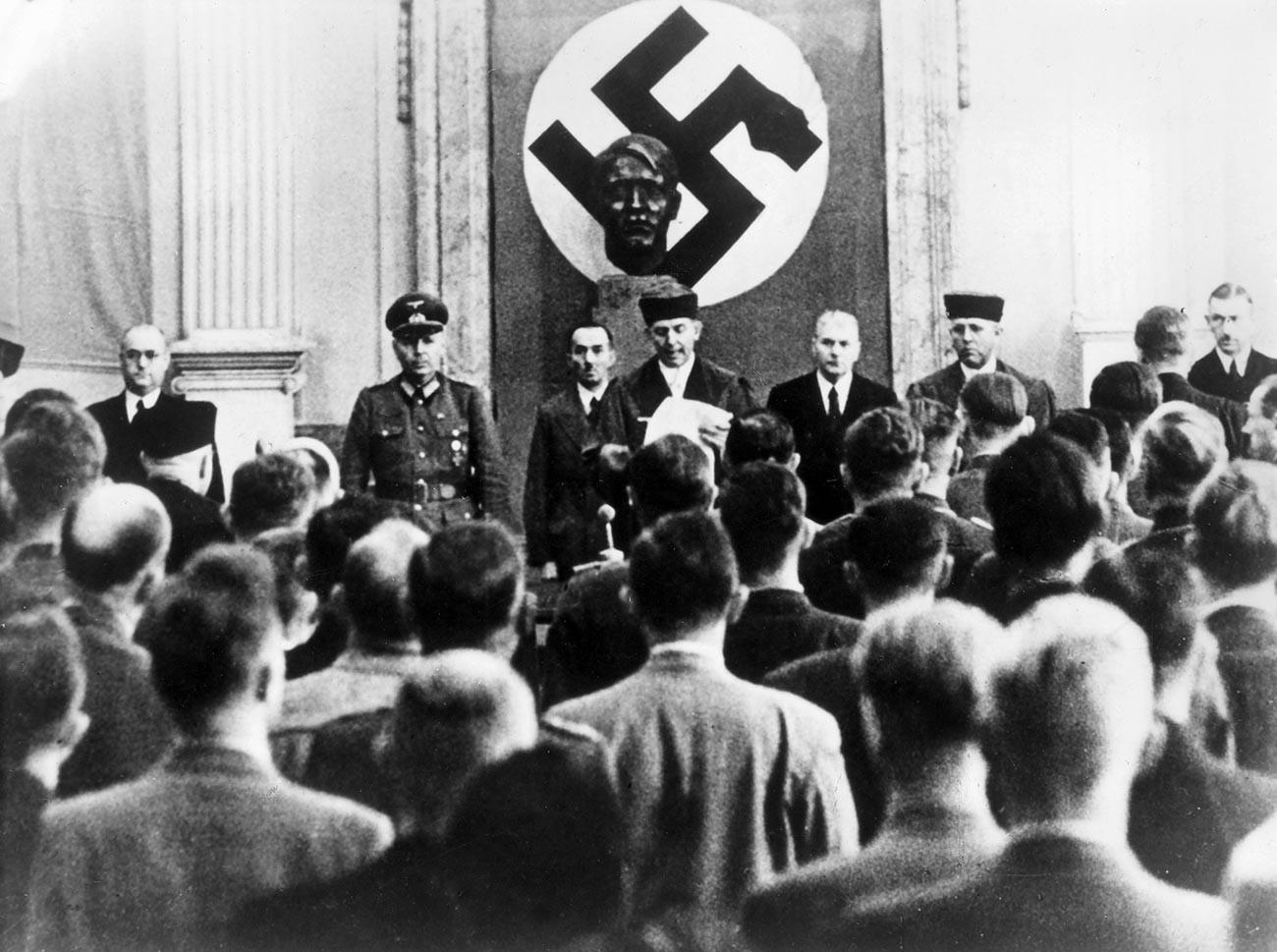 Изрицање казне у судници Врховног суда у Берлину. Роланд Фрajслер (у средини), председавајући народног суда, чита пресуду. Са његове леве стране је генерал Херман Рејнеке, шеф генералштаба.