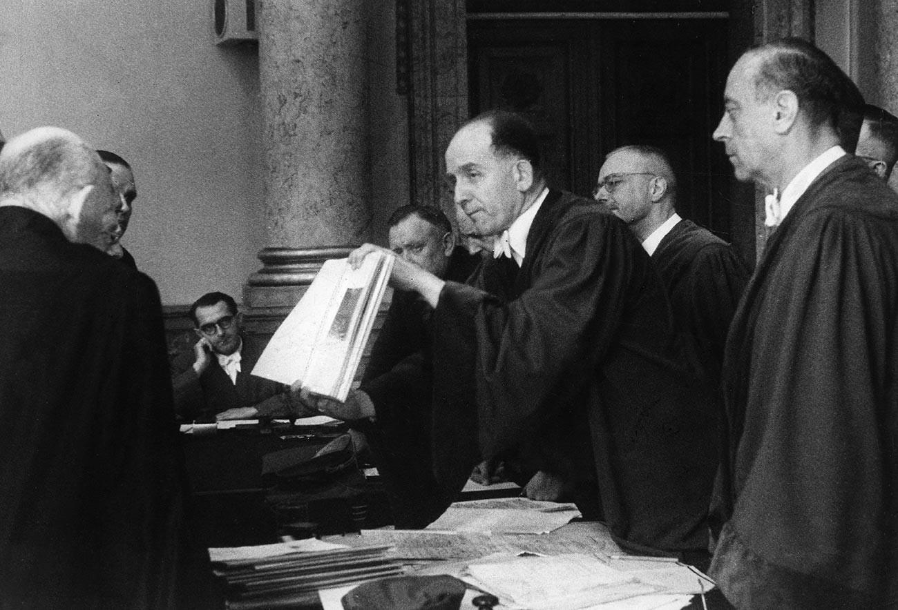 """Суђење у Врховном народном суду у Берлину: председавајући судија Роланд Фрајслер показује фотографије Хитлеровог седишта """"Вучја јазбина"""" (Wolfsschanze) у близини Кентшина (Растенбурга) у Источној Прусији након покушаја атентата. Поред Фрајслера је врховни тужилац Рајха."""