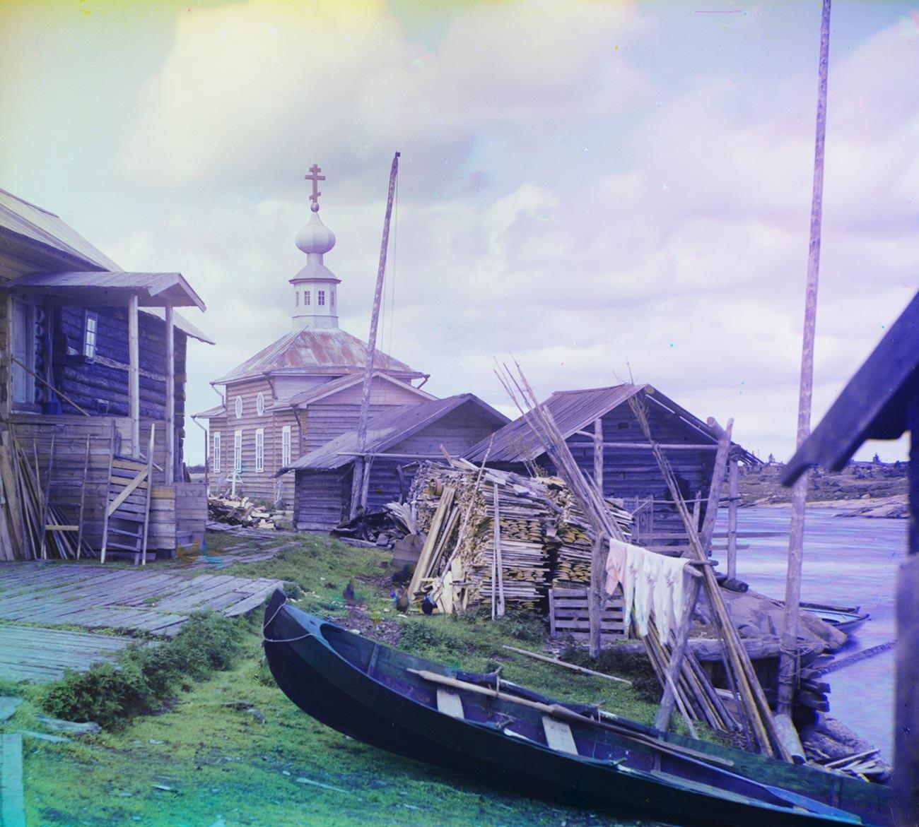 Soroka village (now Belomorsk). House overlooking Vyg River, with skiff, firewood & log sheds. Background: Church of Sts. Zosima & Savvaty. Summer 1916