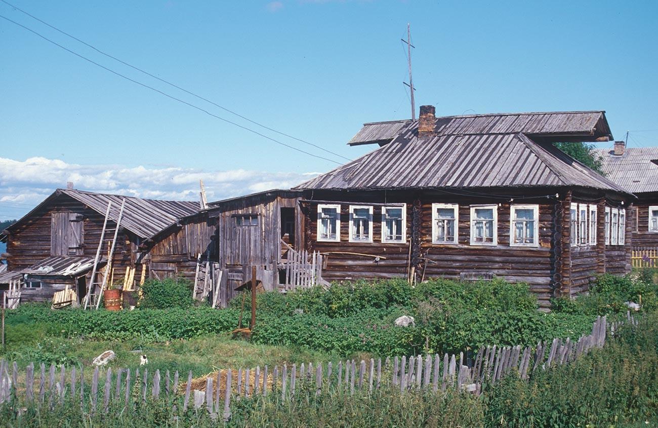 Kovda. Maison en rondins et grange. Notez les pignons à capuchon sur le toit de la maison. Photographie: William Brumfield. 24 juillet 2001