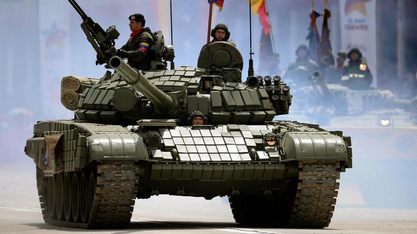Soldados del Ejército venezolano en un tanque T-72S de fabricación rusa marchan durante una ceremonia militar para conmemorar el primer aniversario de la muerte del presidente Hugo Chávez, en Caracas el 5 de marzo de 2014.