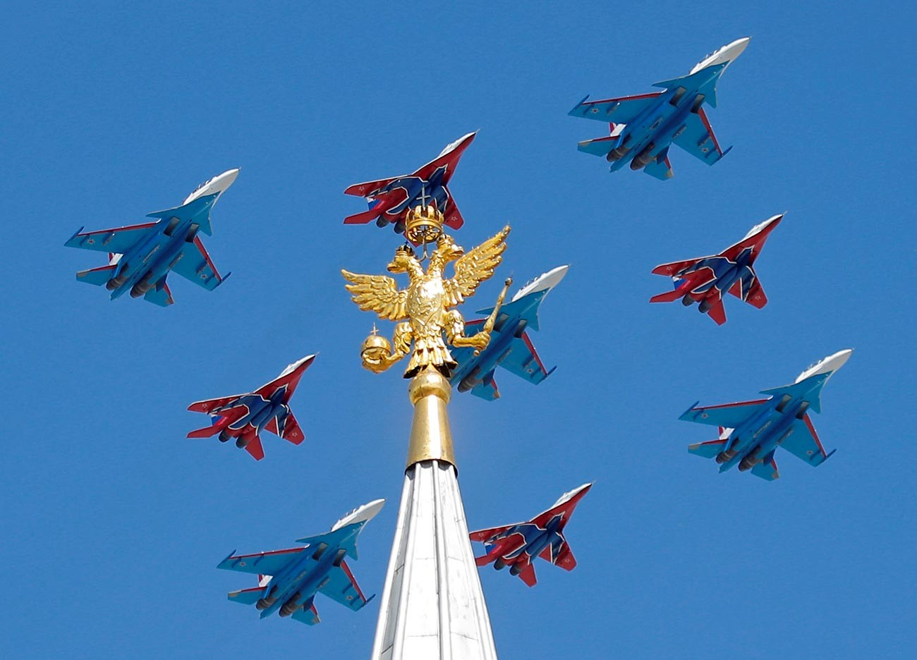 Jet tempur MiG-29 regu aerobatik Strizhi dan jet tempur Su-30 regu aerobatik Russkiye Vityazi terbang dalam formasi selama parade Hari Kemenangan di Moskow.