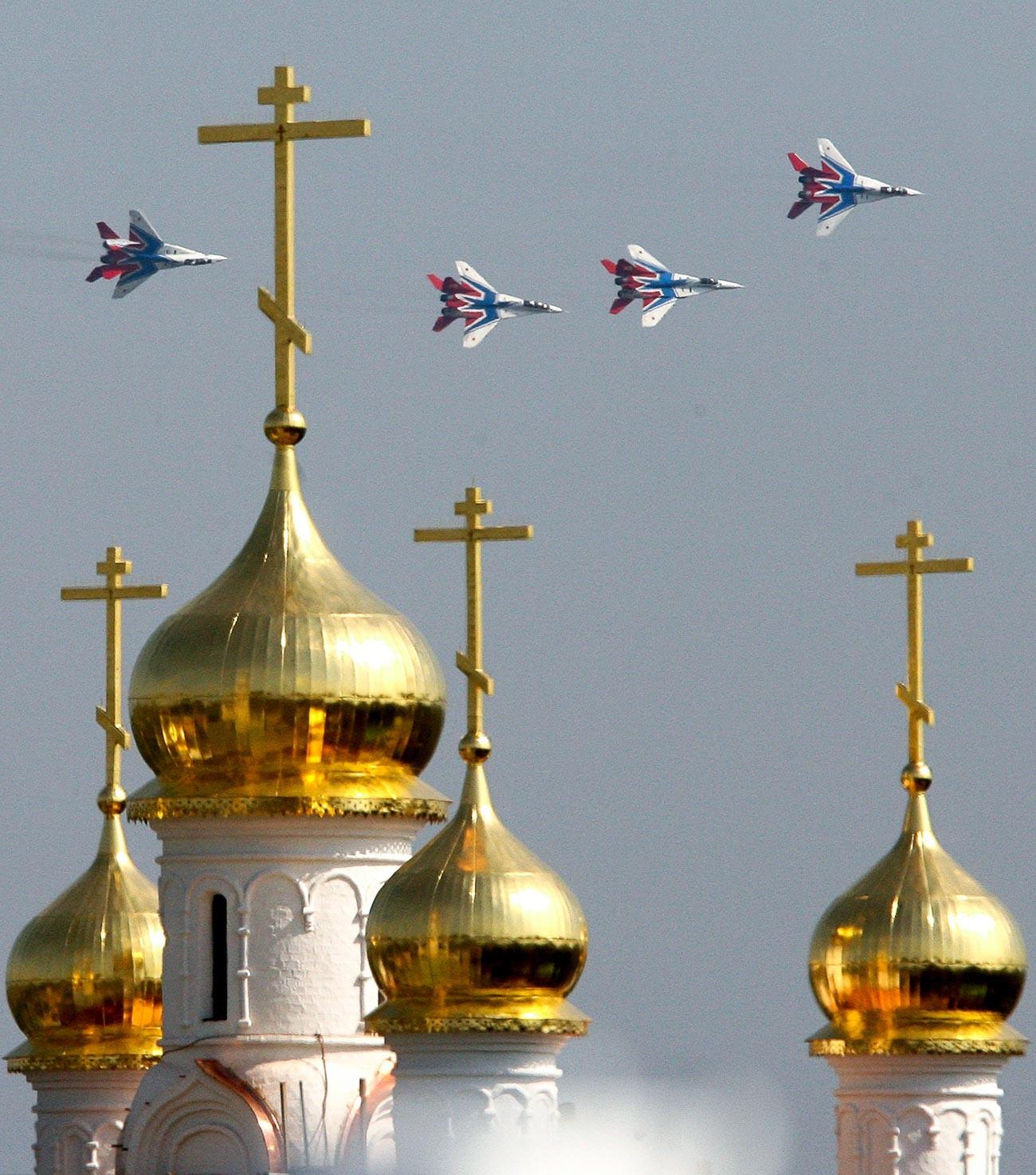Jet tempur MiG-29 regu aerobatik Strizhi terbang dalam formasi di atas gereja Ortodoks selama pertunjukan udara internasional MAKS 2007 di Zhukovsky.