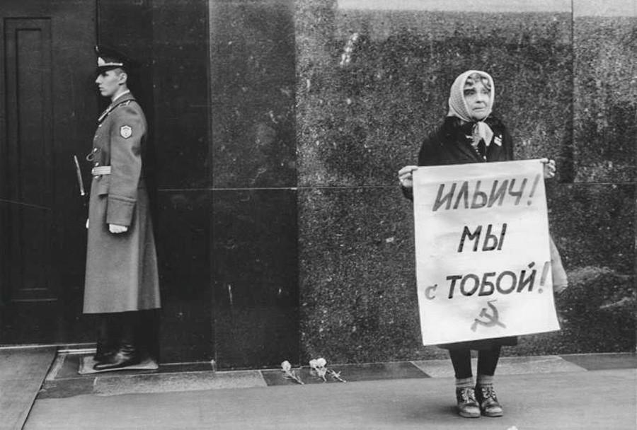 """Eine Frau bei einer Kundgebung in der Nähe des Lenin-Mausoleums: Auf dem Plakat steht: """"Iljich [Lenin], wir sind bei dir!"""""""