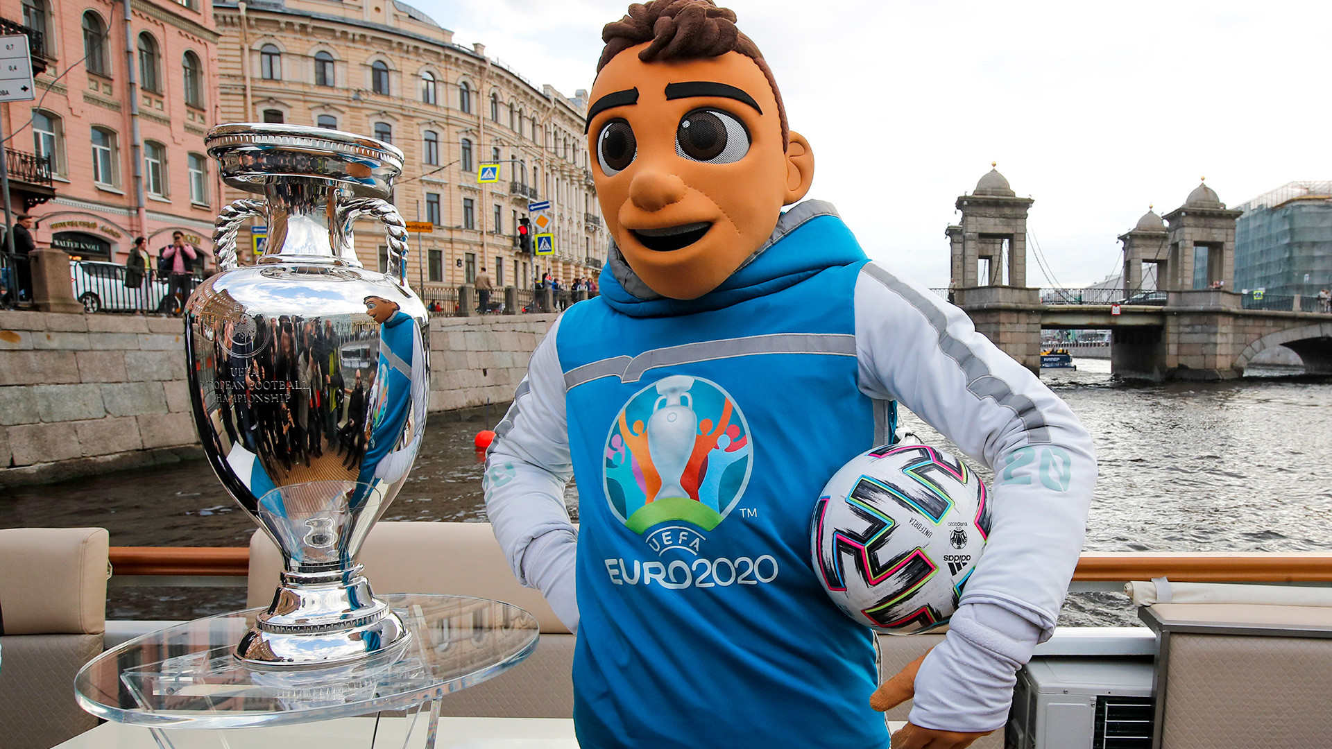 EURO 2020 championship mascot Skillzy poses with the EURO 2020 trophy traveling on a boat down the Fontanka River during the official EURO 2020 trophy's tour in St.Petersburg, Russia, Saturday, May 22, 2021. St. Petersburg will host seven postponed UEFA EURO 2020 matches, including a quarter final.